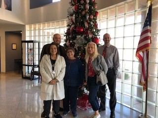 The DAC Committee posing in front of Christmas Tree